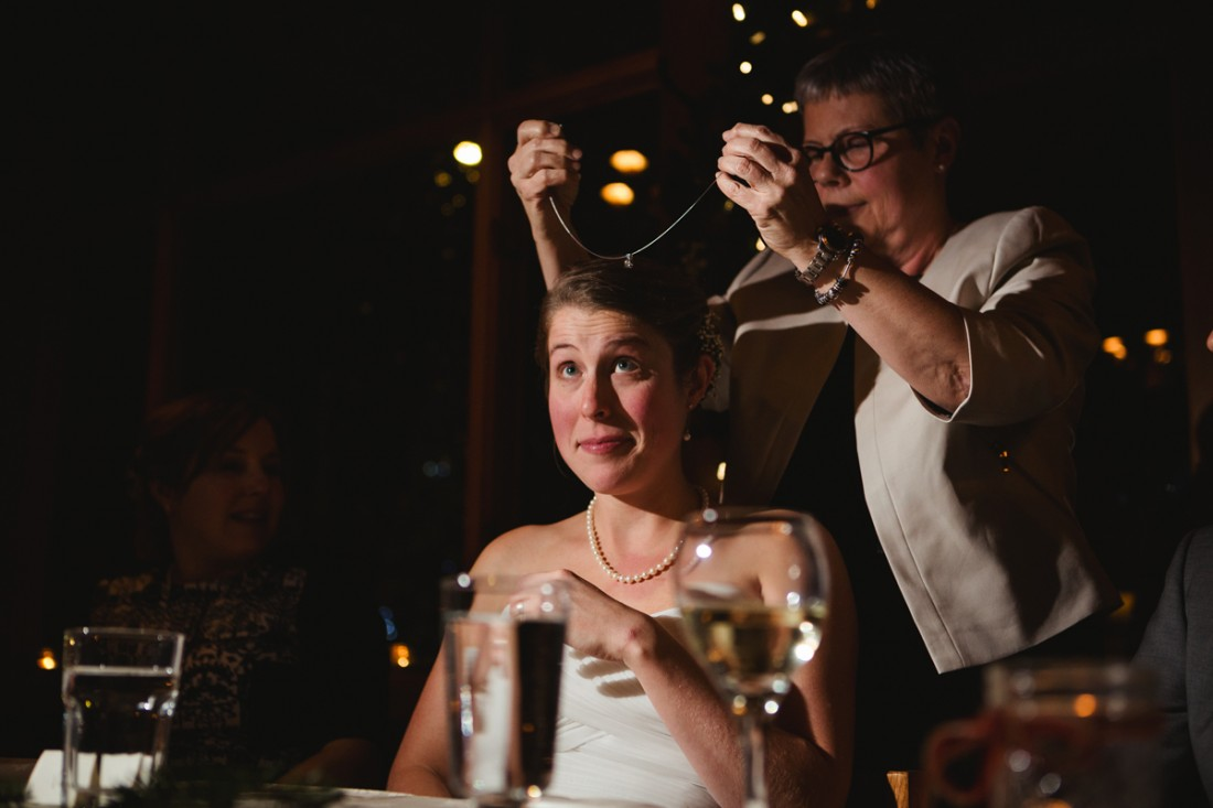 bride's mother giving her a necklace as wedding gift and she is putting the necklace on the bride's neck