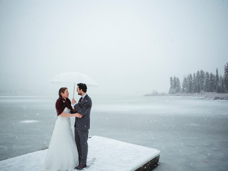 Couple in front of an icy lake under sunset light with flying shinning snow flake after their wedding ceremony in edgewater lodge, Whistler