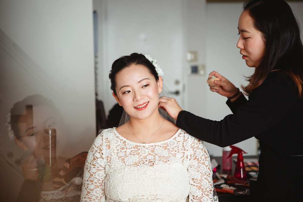 bride having her hair done at home in downtown montreal by the make up artist and fashion designer Kelly and heading to vieux port steakhouse for her winter intimate wedding