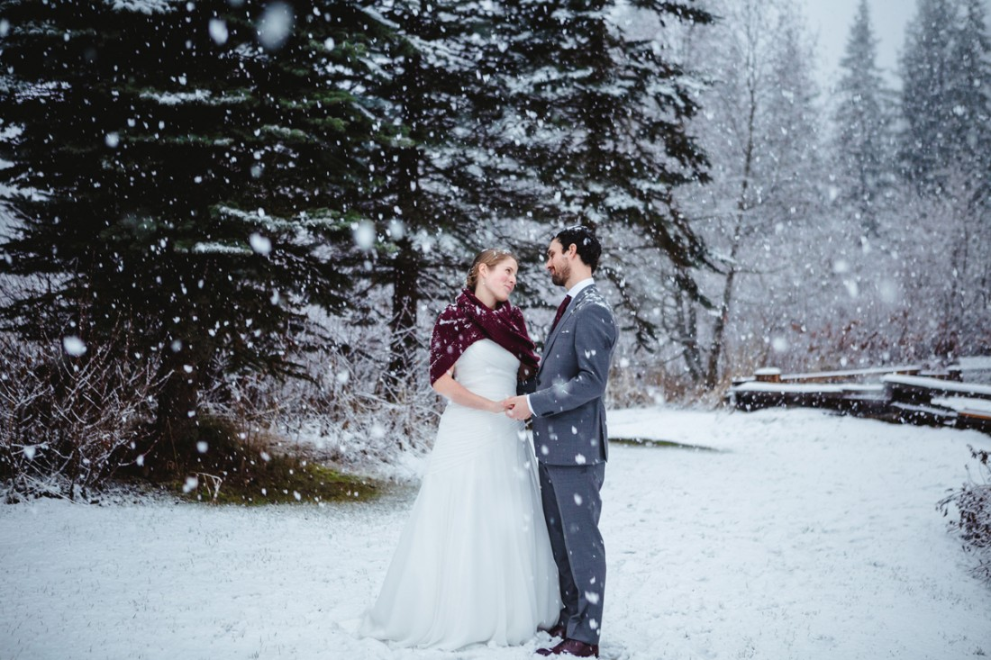 couple walking in the forest under the snow in whistler for their destination wedding