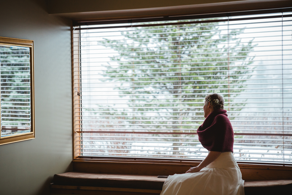 bride looking through the window and waiting for her father to pick her up for the outdoor ceremony in edgewater lodge, whistler