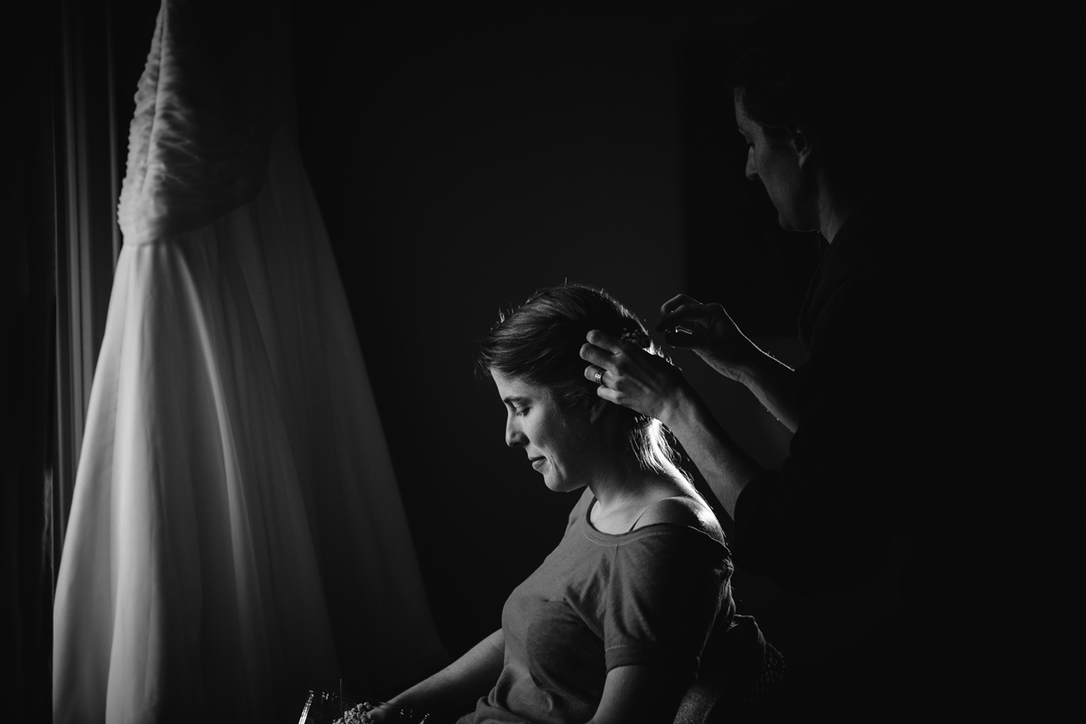 black and white photo of bride having her hair done in front of the window the room of edgewater lodge, whistler for her winter destination wedding