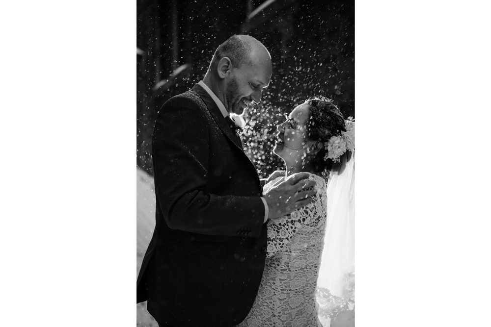 bride and groom having a fun moment with snow splashing after the ceremony under snow in an alley of old port, montreal