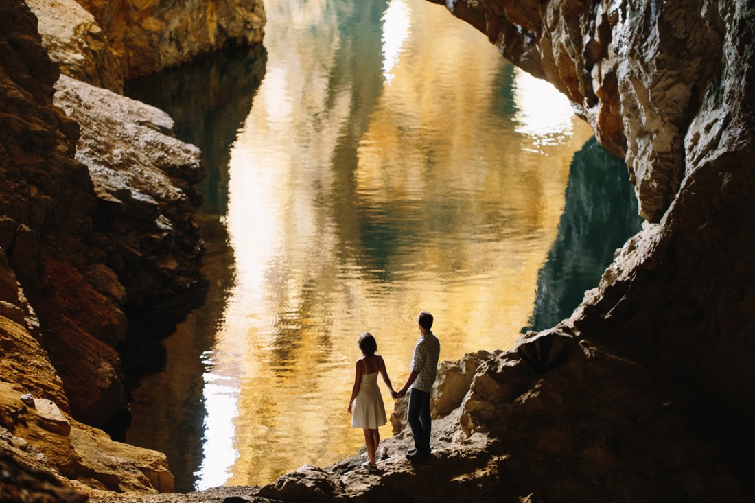 engaged couple standing in front_of an orange lake inside of a huge cave in quebec