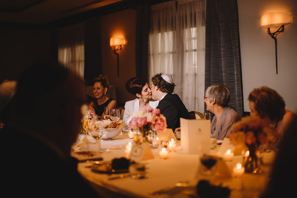 Bride and groom kissing during the reception in Ritz Carlton Montreal surrounded by fresh Peony and families.