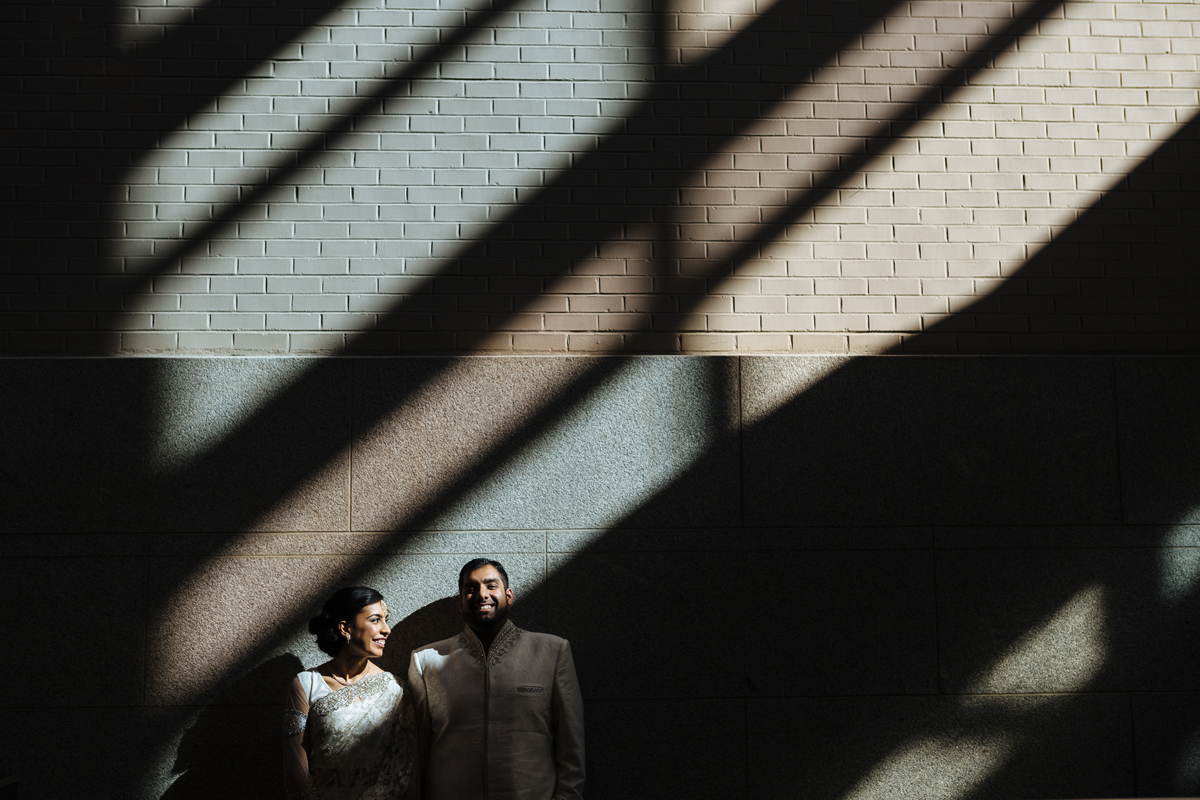 Indian bride wearing sari with groom under a strap of window light in world trade center Montreal