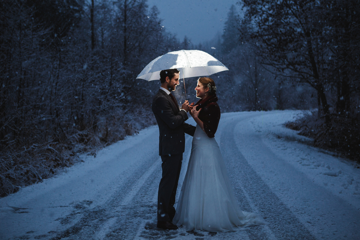 Fairy tale like wedding-newlyweds with umbrella under snowflake on the road towards the forest in whistler