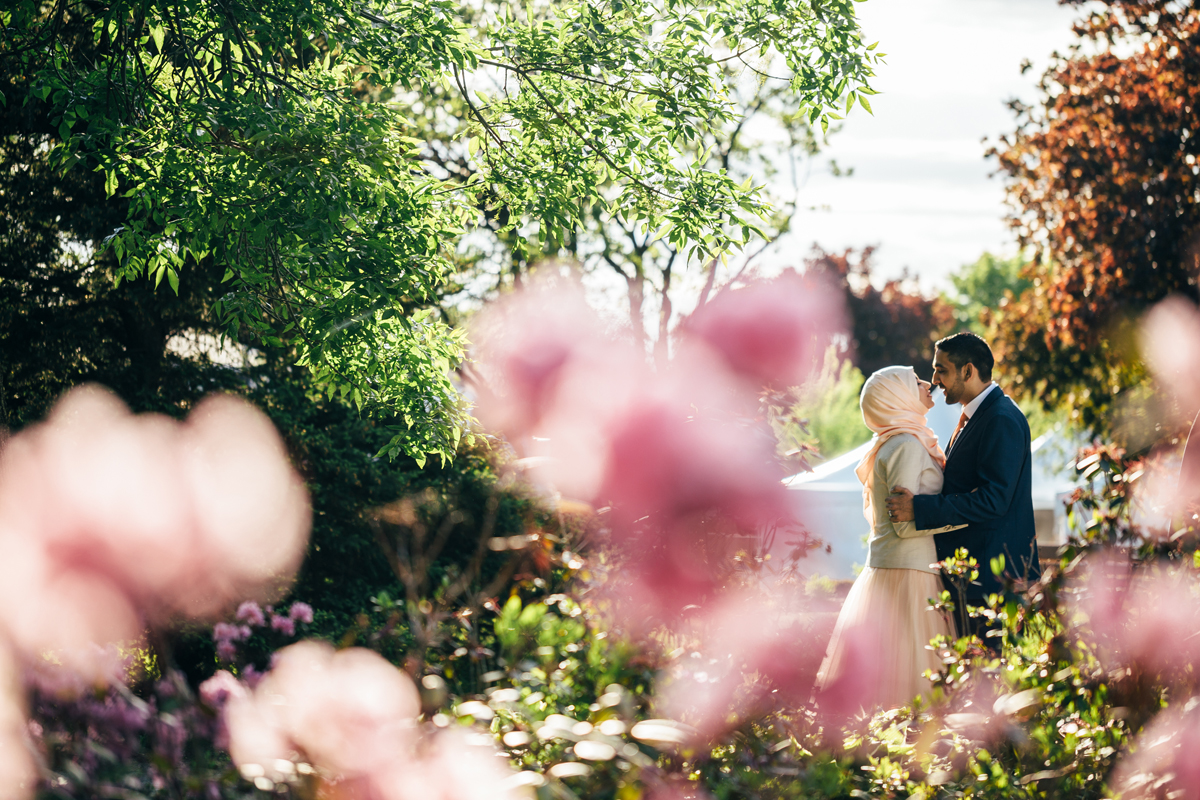 After the Islamic wedding ceremony in Laval, persian bride and indian groom are having fun surrounded by colorful flower in Natural Center of Laval