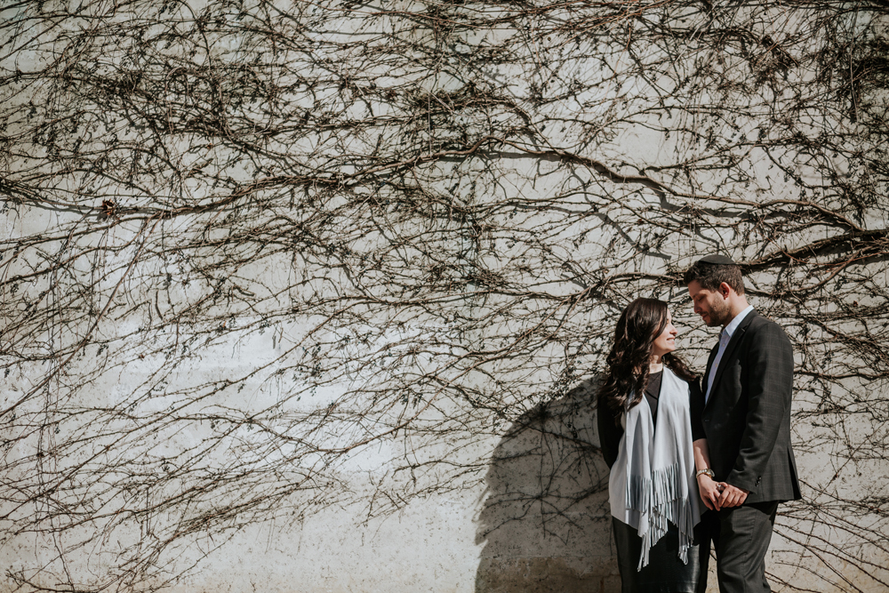 Engagement-couple-surprise-proposal-couple-in-front-of-wall-climbing-plants